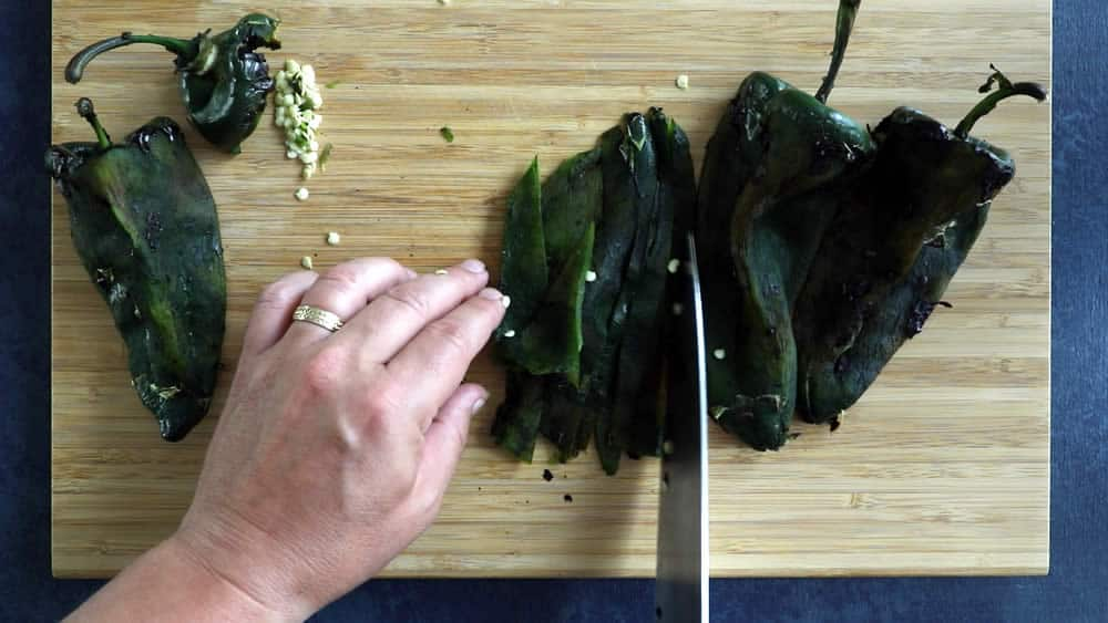 "Slicing the roasted poblano peppers into strips, or ""rajas"""