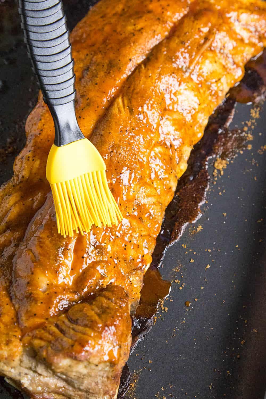 Brushing the honey-sriracha sauce on the oven baked ribs