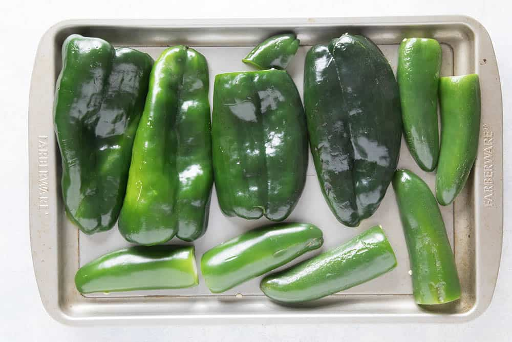Poblano peppers and jalapeno peppers, sliced and on a baking sheet, ready to roast