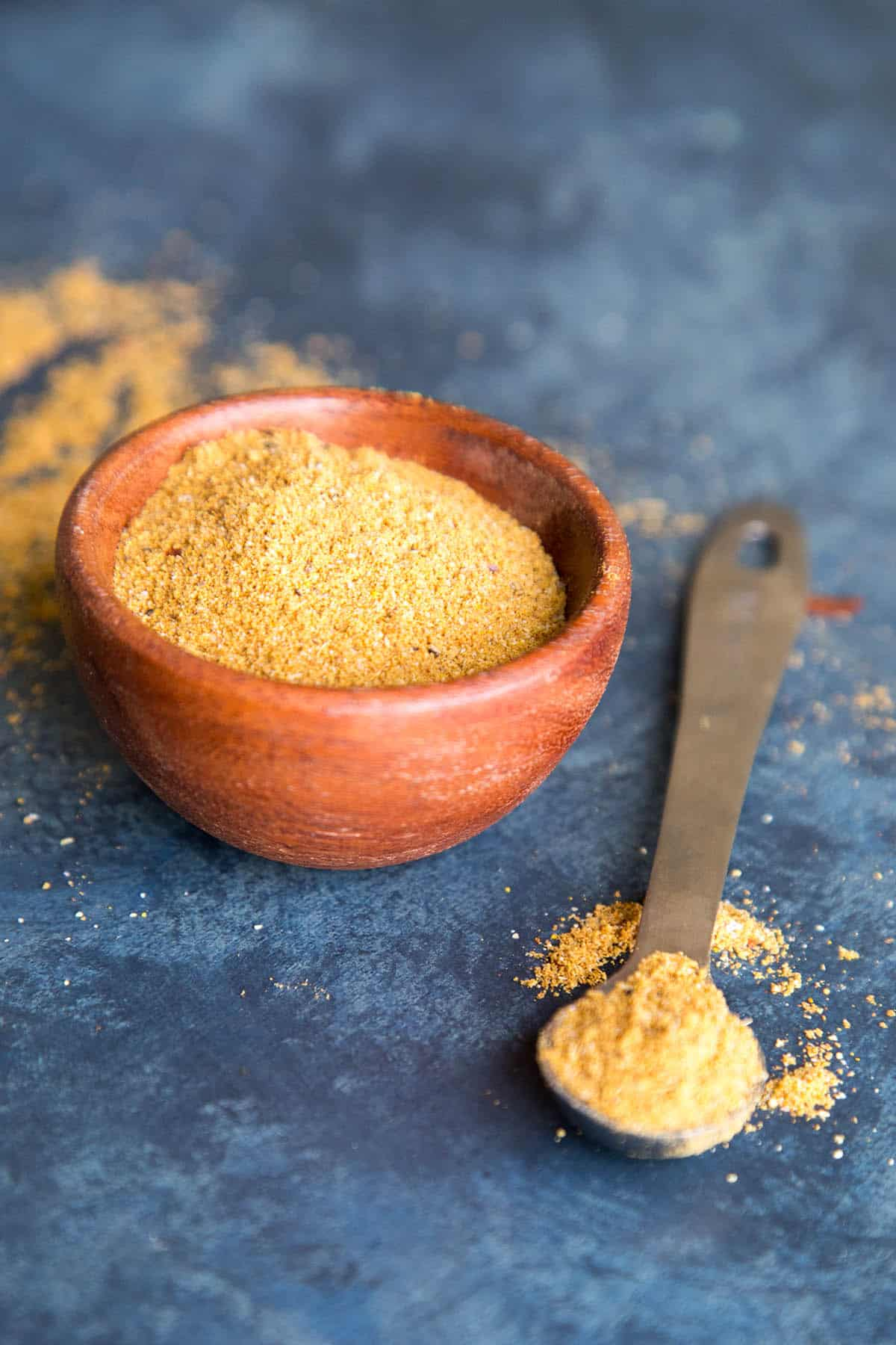 Vindaloo curry seasoning blend in a bowl and on a measuring spoon.