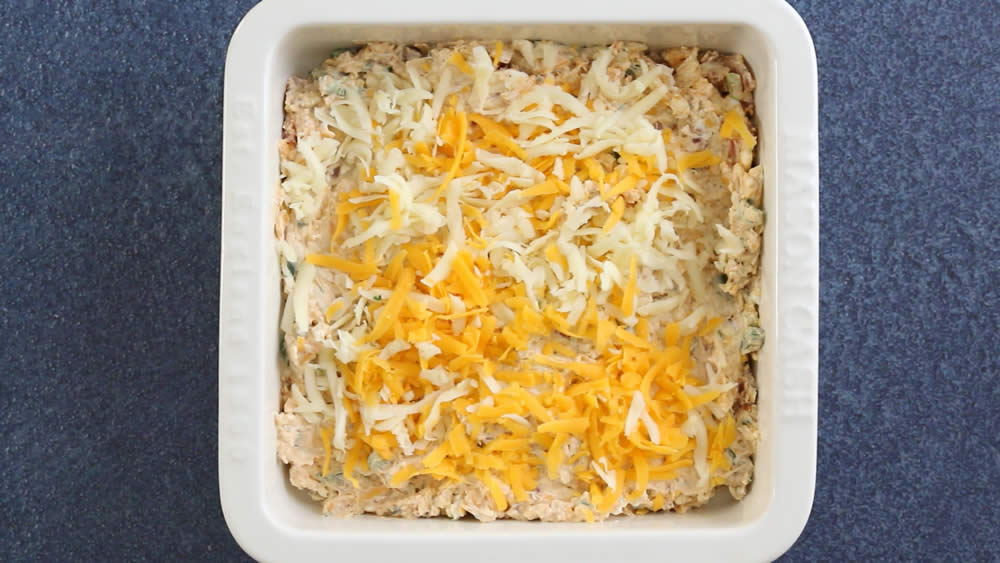 Bacon Jalapeno Popper Dip, topped with cheese, ready for the oven