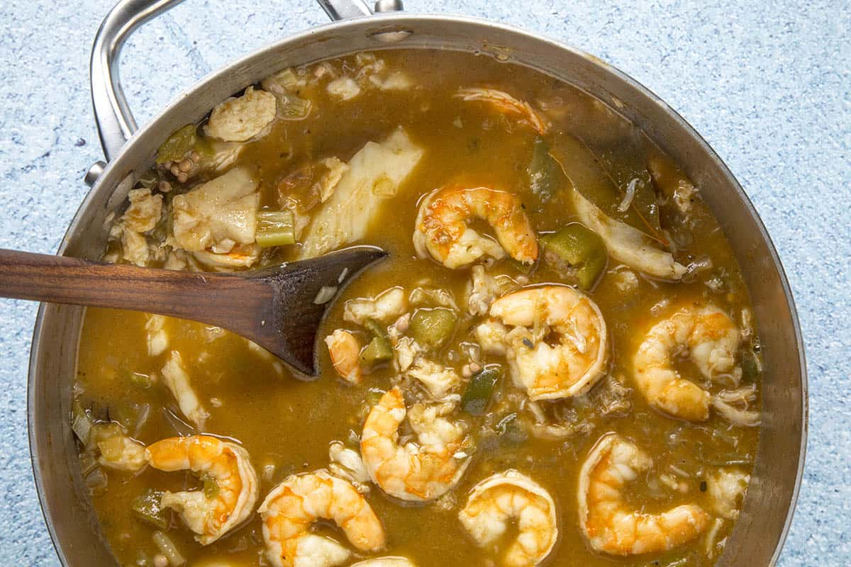 Seafood Gumbo in a pot, being stirred