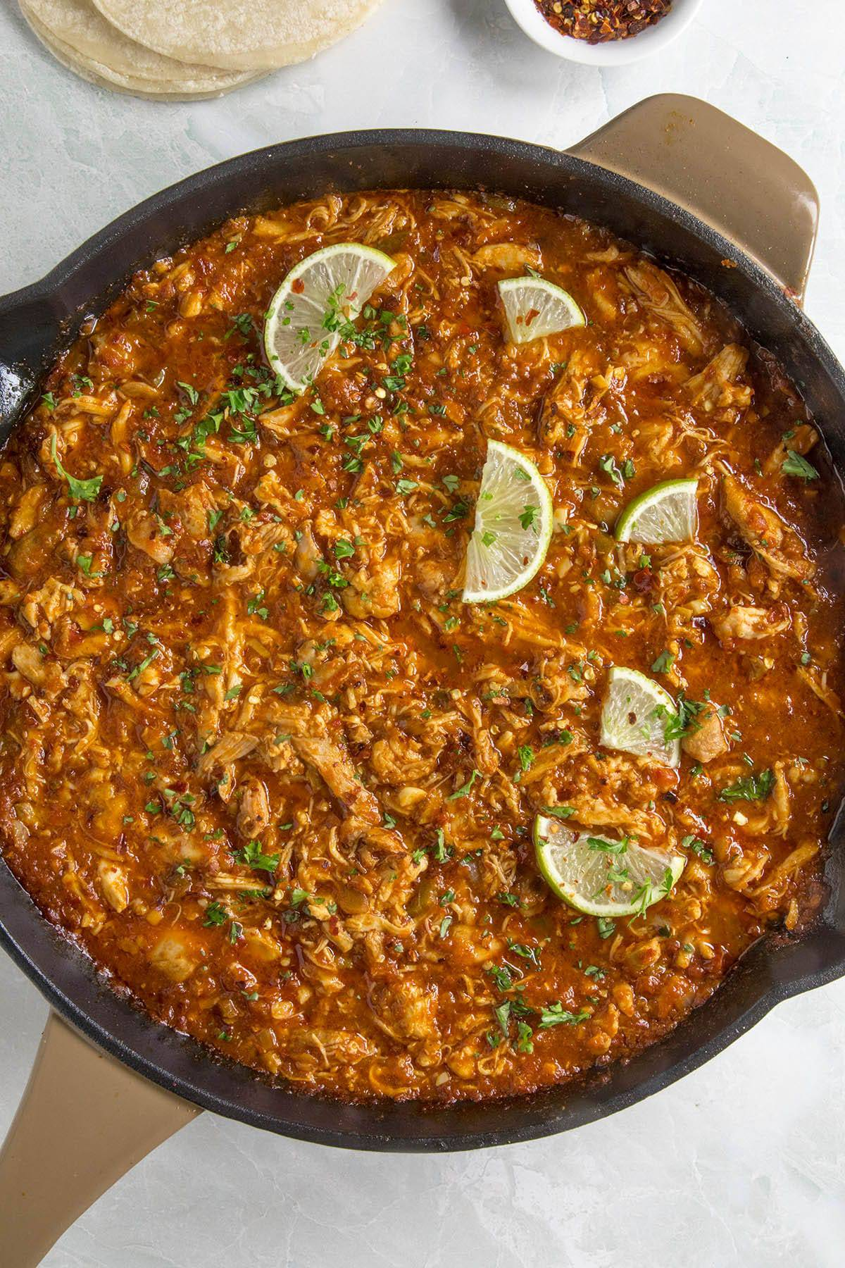 Chicken Tinga in a pan with lime slices