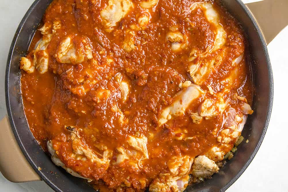 Chicken thighs simmering in our tomato-chipotle sauce for chicken tinga