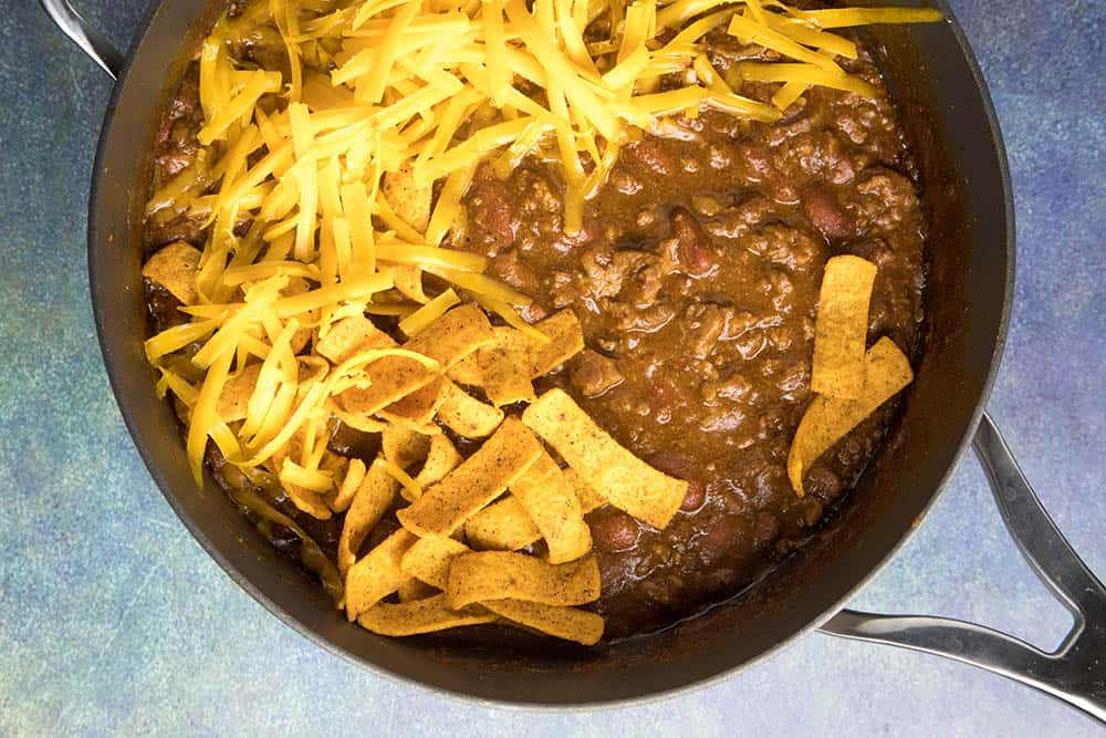 Cincinnati Chili in a pot with shredded cheddar cheese and Fritos over the top