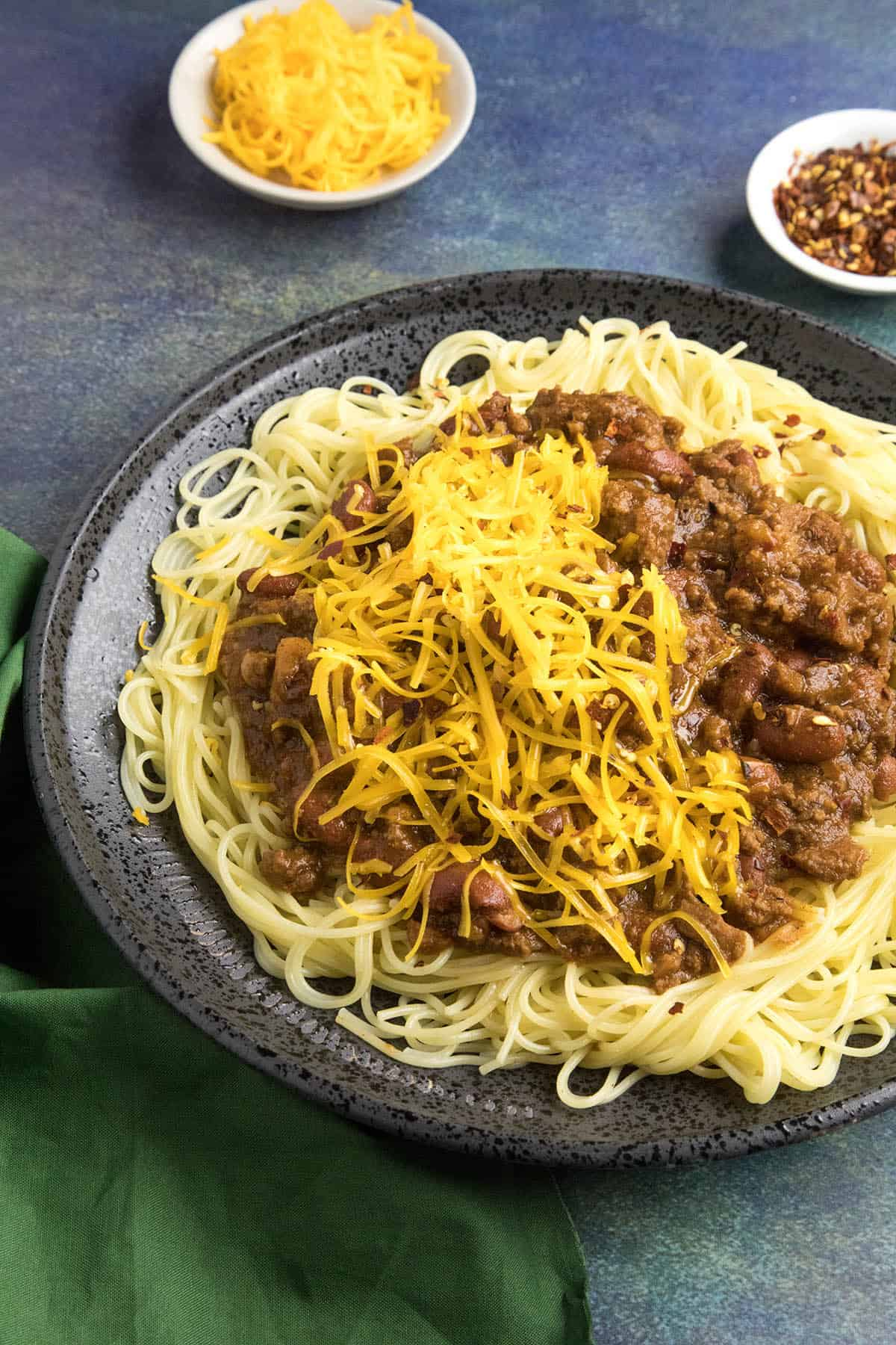 Cincinnati Chili on a plate of noodles with shredded cheddar cheese over the top, ready to eat