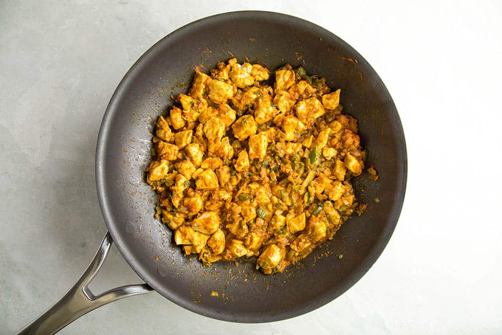 Add the curry paste and spicy seasonings to the chicken
