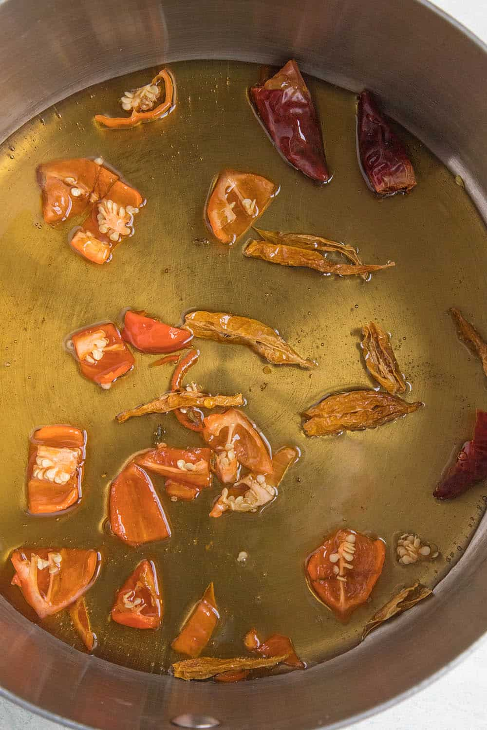 Simmering honey with hot peppers to infuse them with flavor and heat
