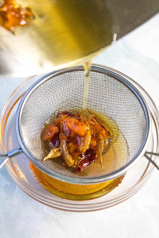 Straining the infused hot honey