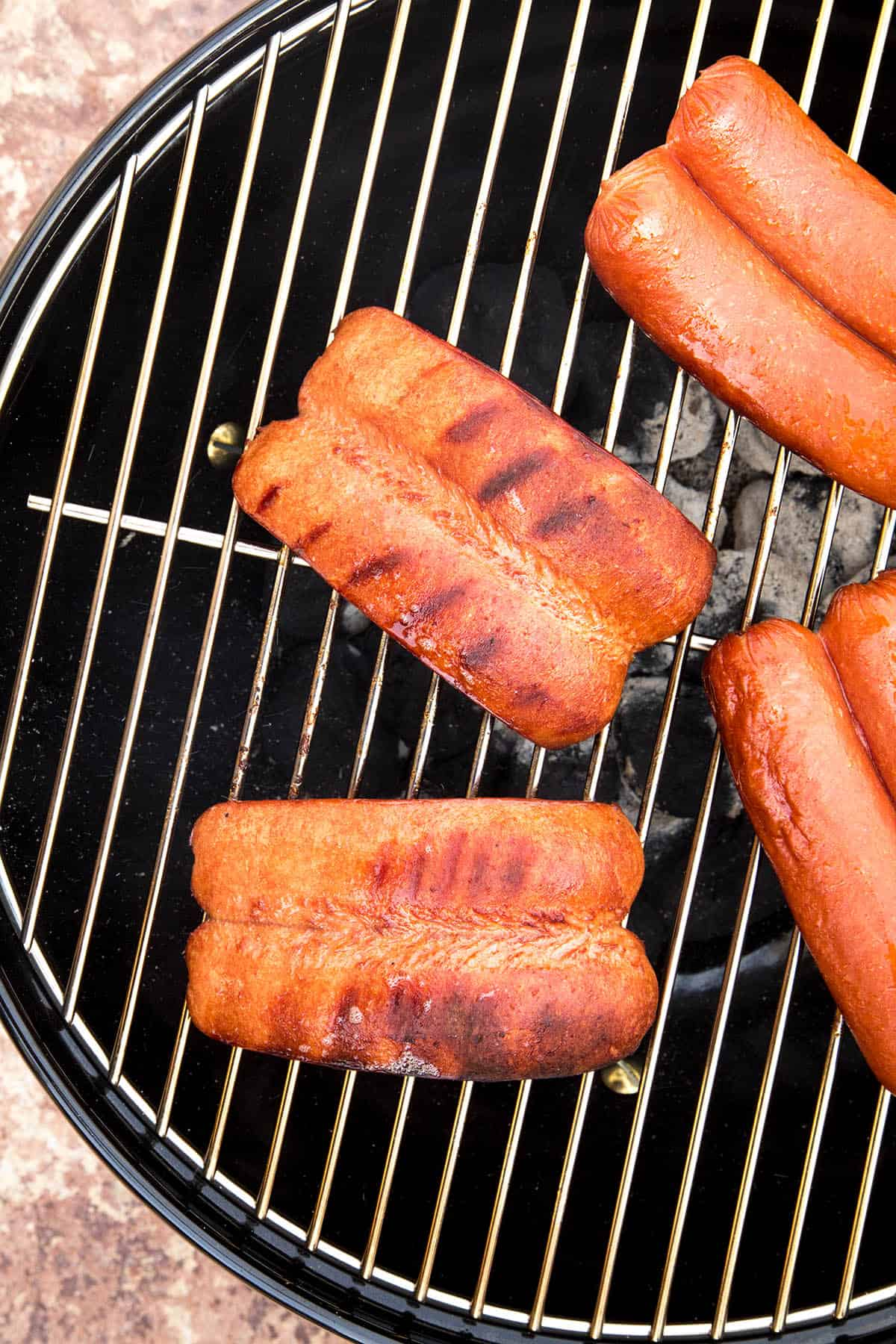 Charred hot dogs on the grill