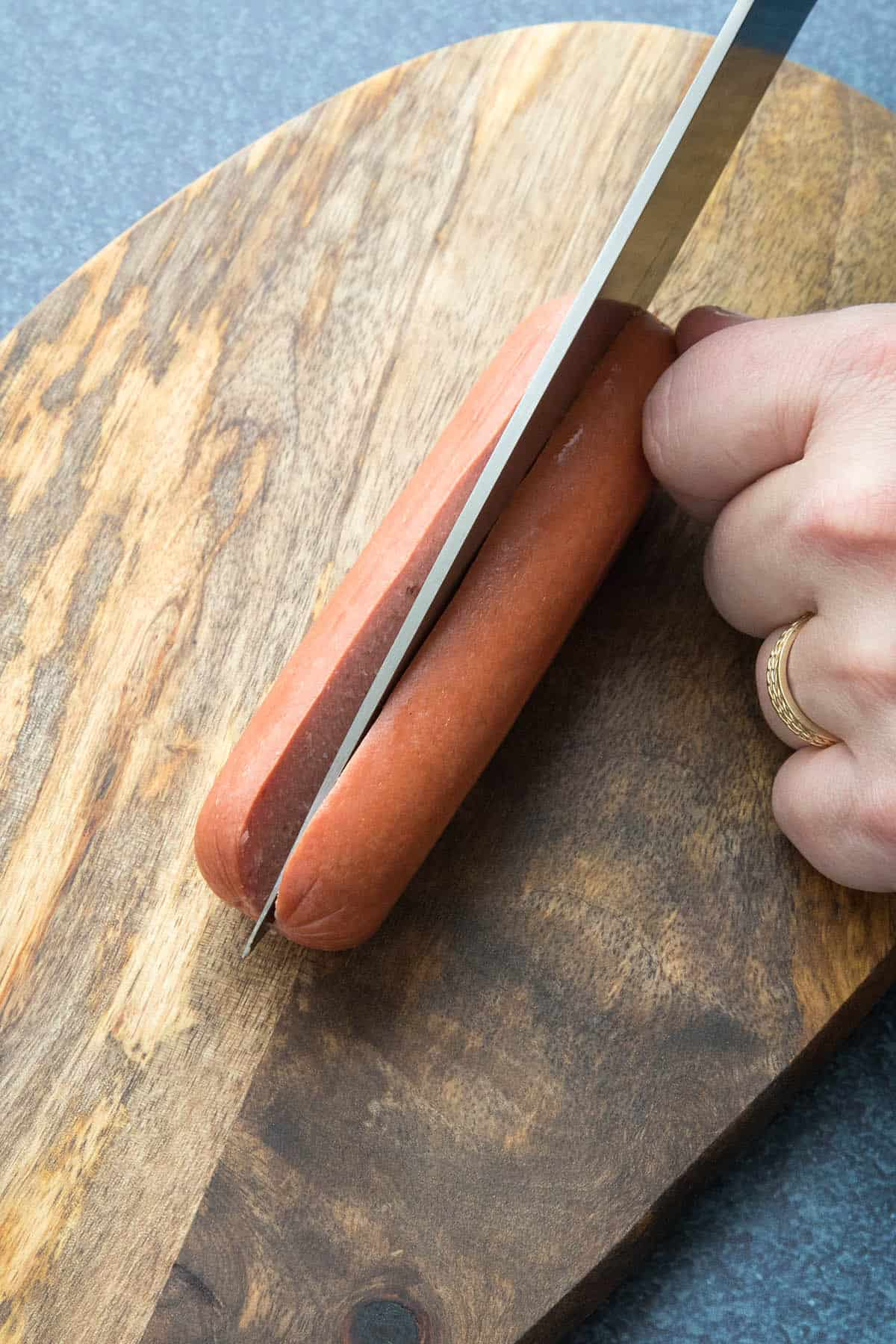 Slicing an all beef hot dog open to make Chicago style char dogs