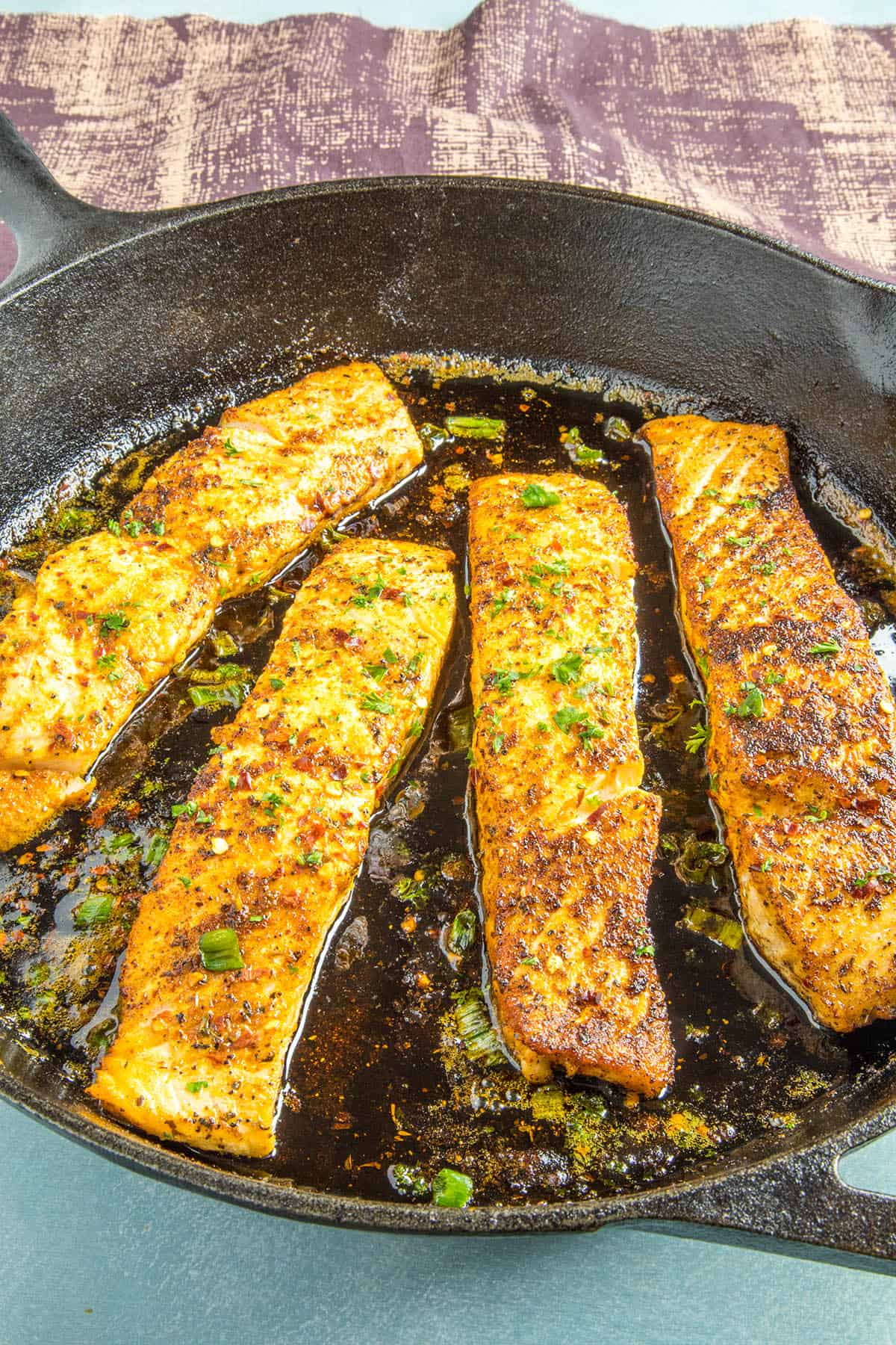 Blackened Salmon in a pan with garnish