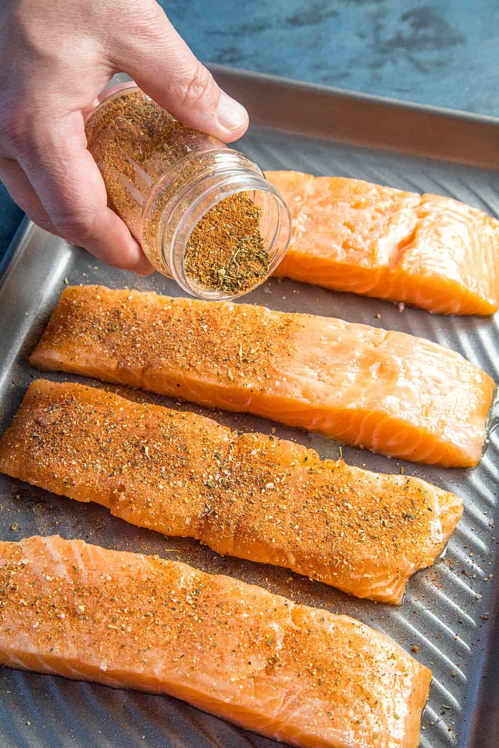 Seasoning the salmon with blackening seasoning