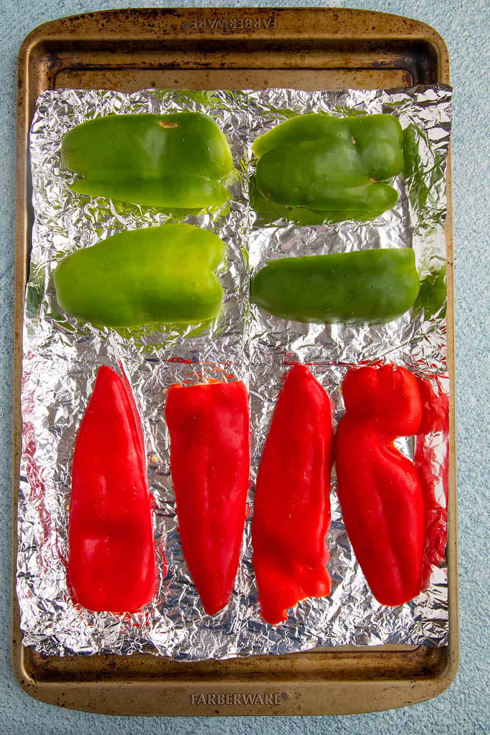 Peppers on a baking sheet, ready to roast in the oven