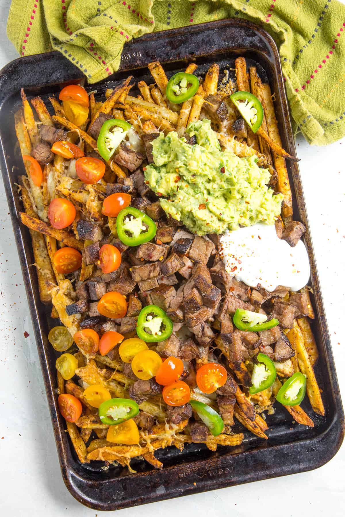 Carne Asada Fries on a baking sheet with lots of fixings