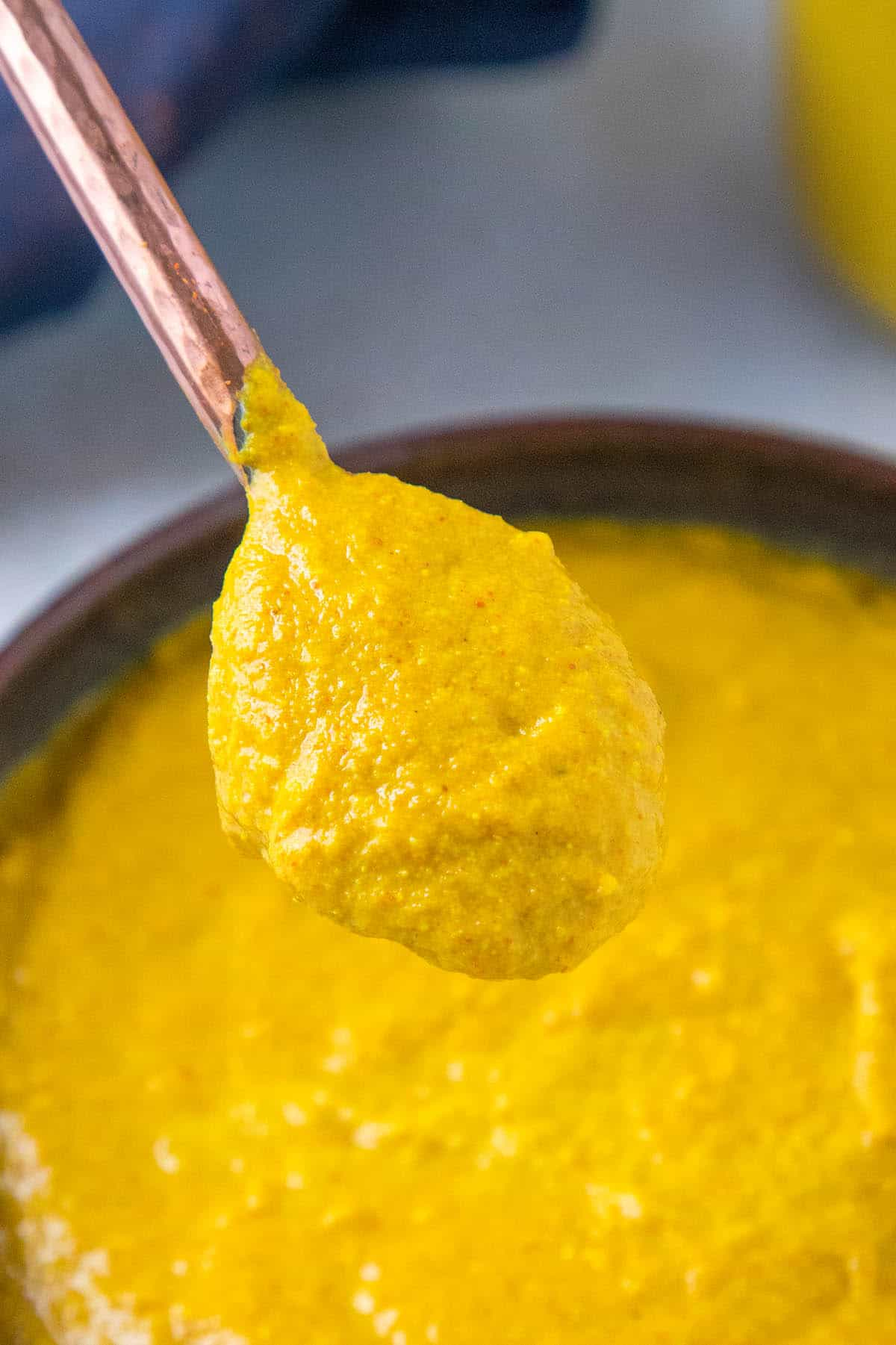 Homemade Yellow Mustard on a spoon, close up