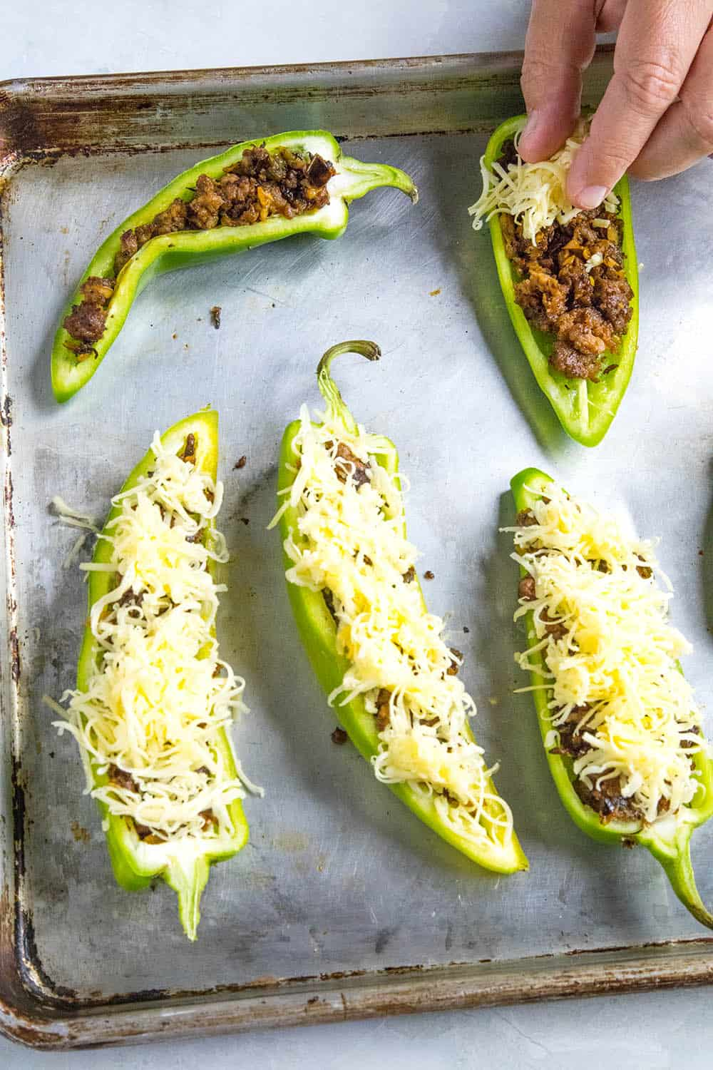 Adding cheese to our stuffed anaheim peppers