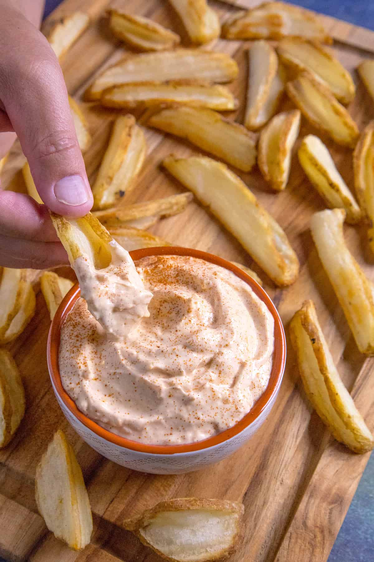 Dipping into the sour cream dip with a potato wedge