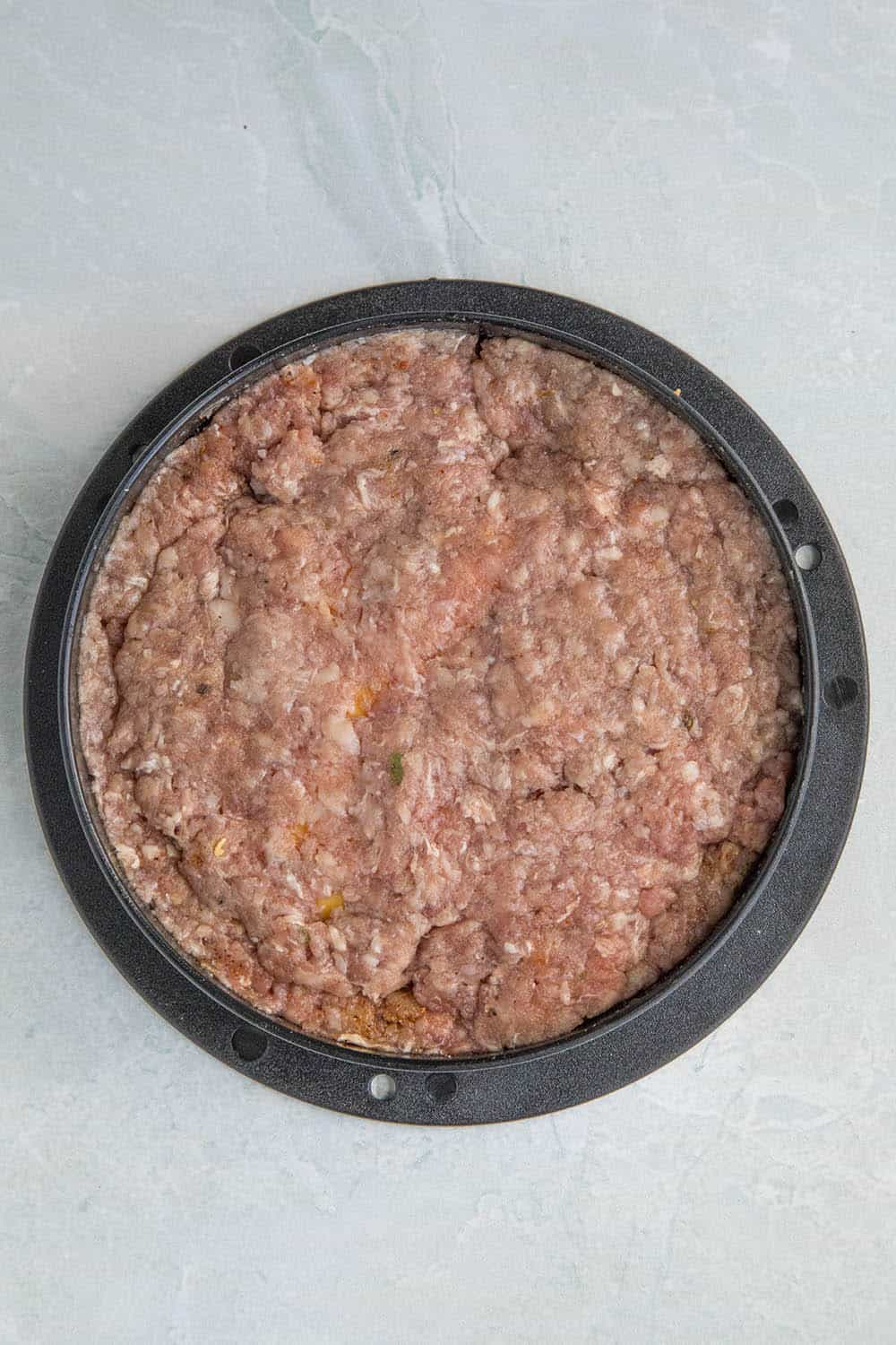 Topping the stuffed burgers with extra ground beef to enclose the cheese