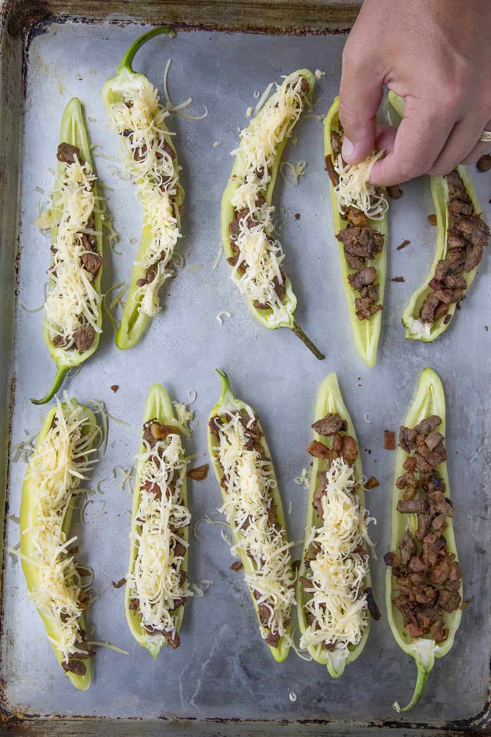 Topping the stuffed banana peppers with cheese