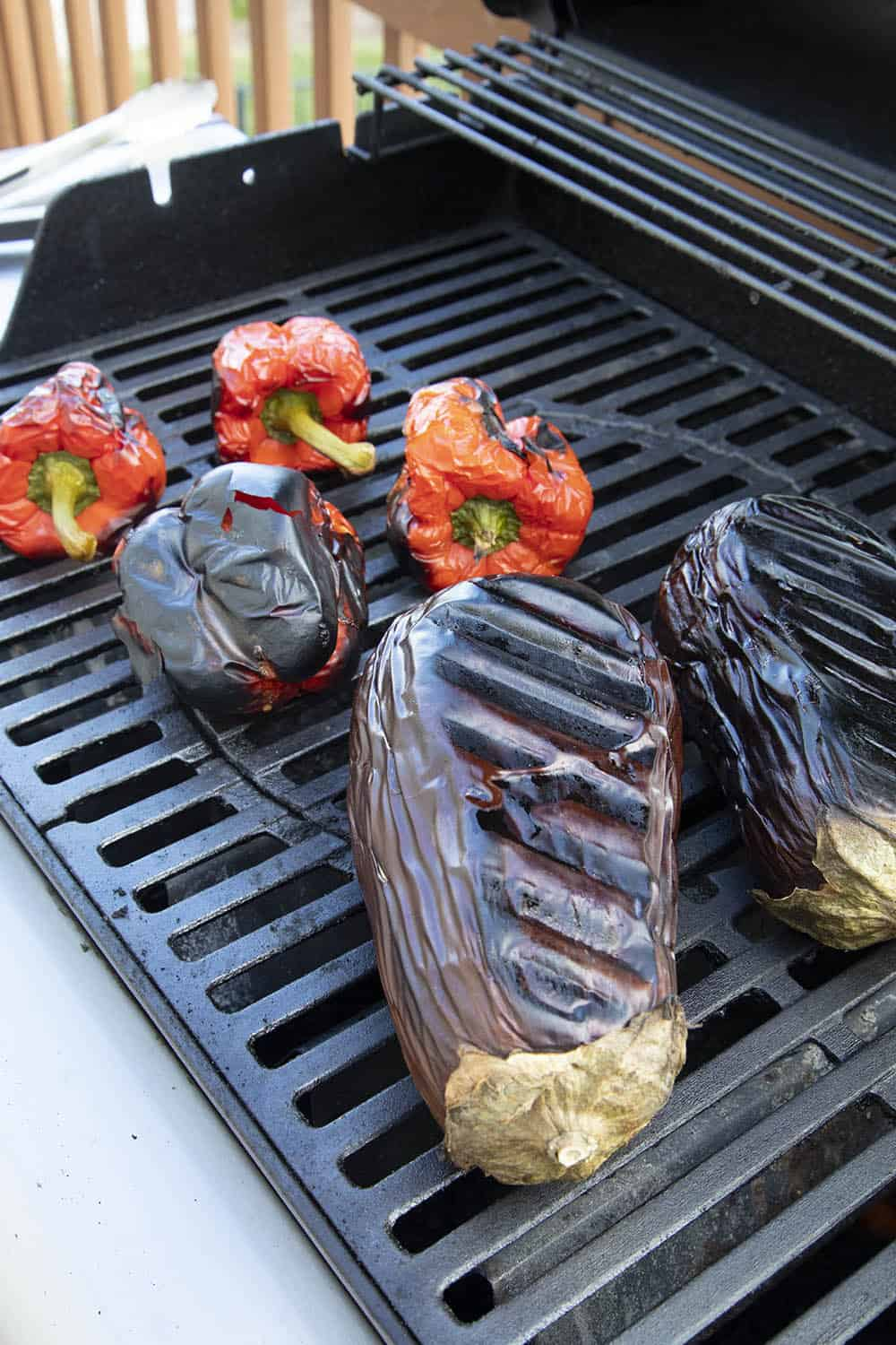 Roasted eggplants and red bell peppers on the grill, just about done cooking