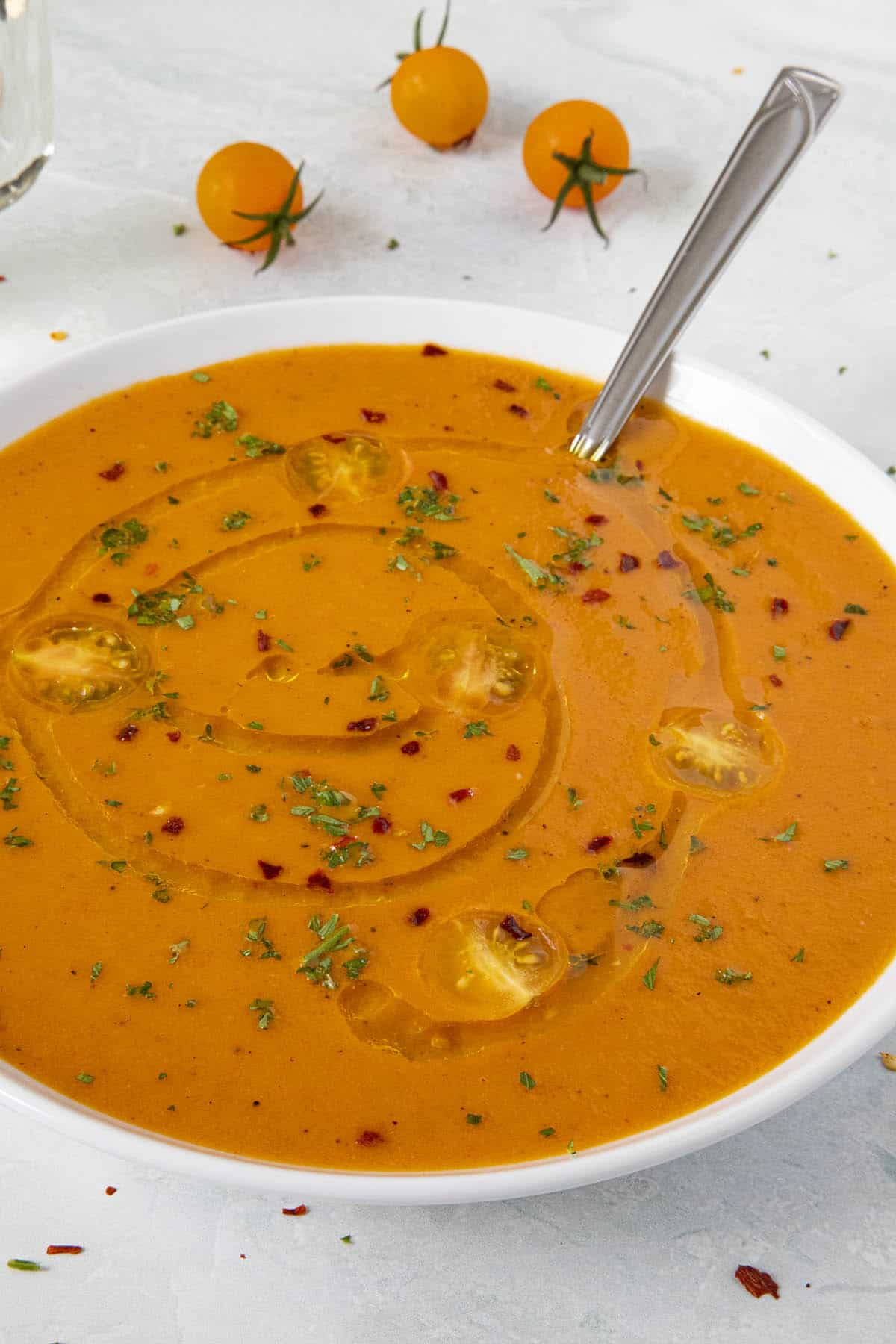 A bowl of Roasted Tomato Soup with spicy chili flakes, sliced cherry tomatoes and a swirl of olive oil on top