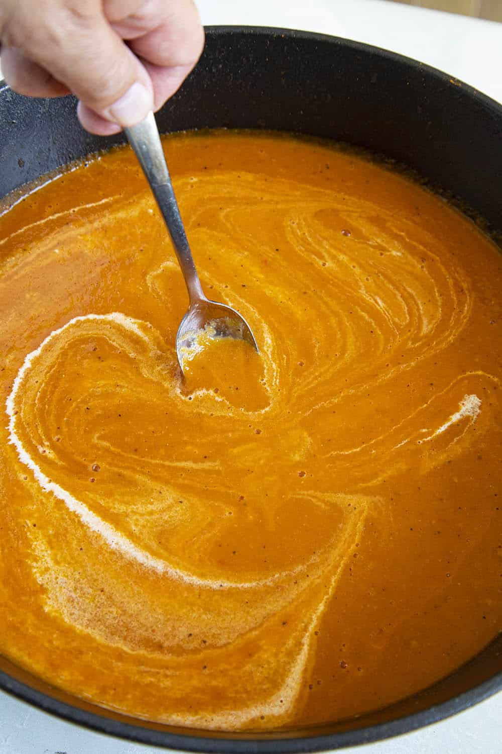 Swirling heavy cream into my roasted tomato soup