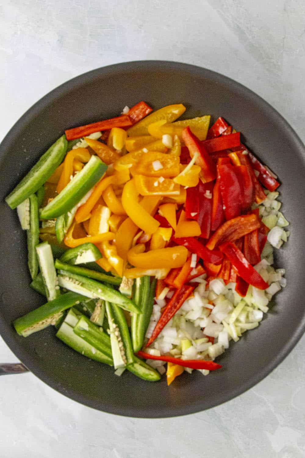 Cooking down the peppers and onions in a pan to make rasta pasta