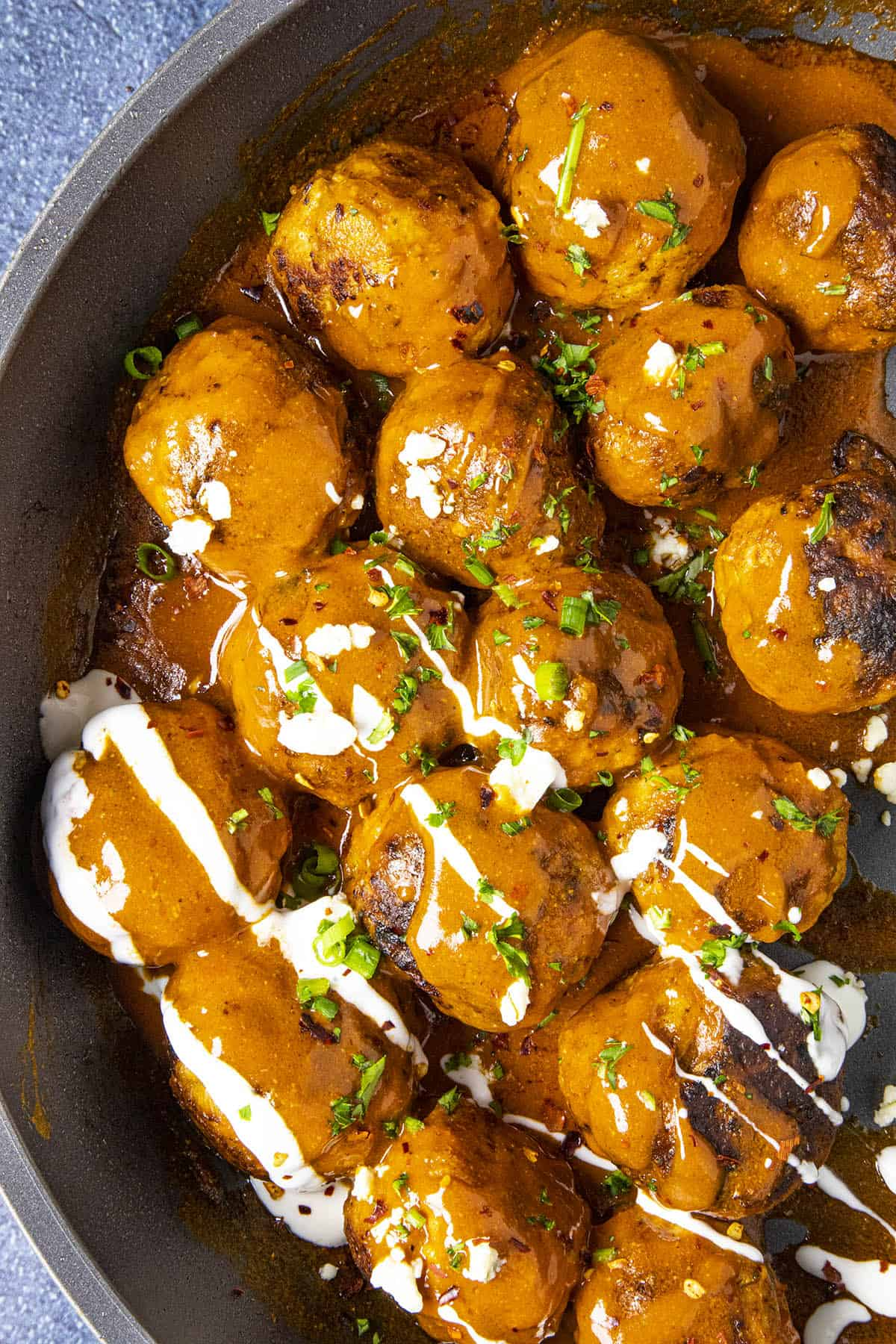 Buffalo Chicken Meatballs on a plate, served up in a pan with blue cheese sauce drizzled over the top