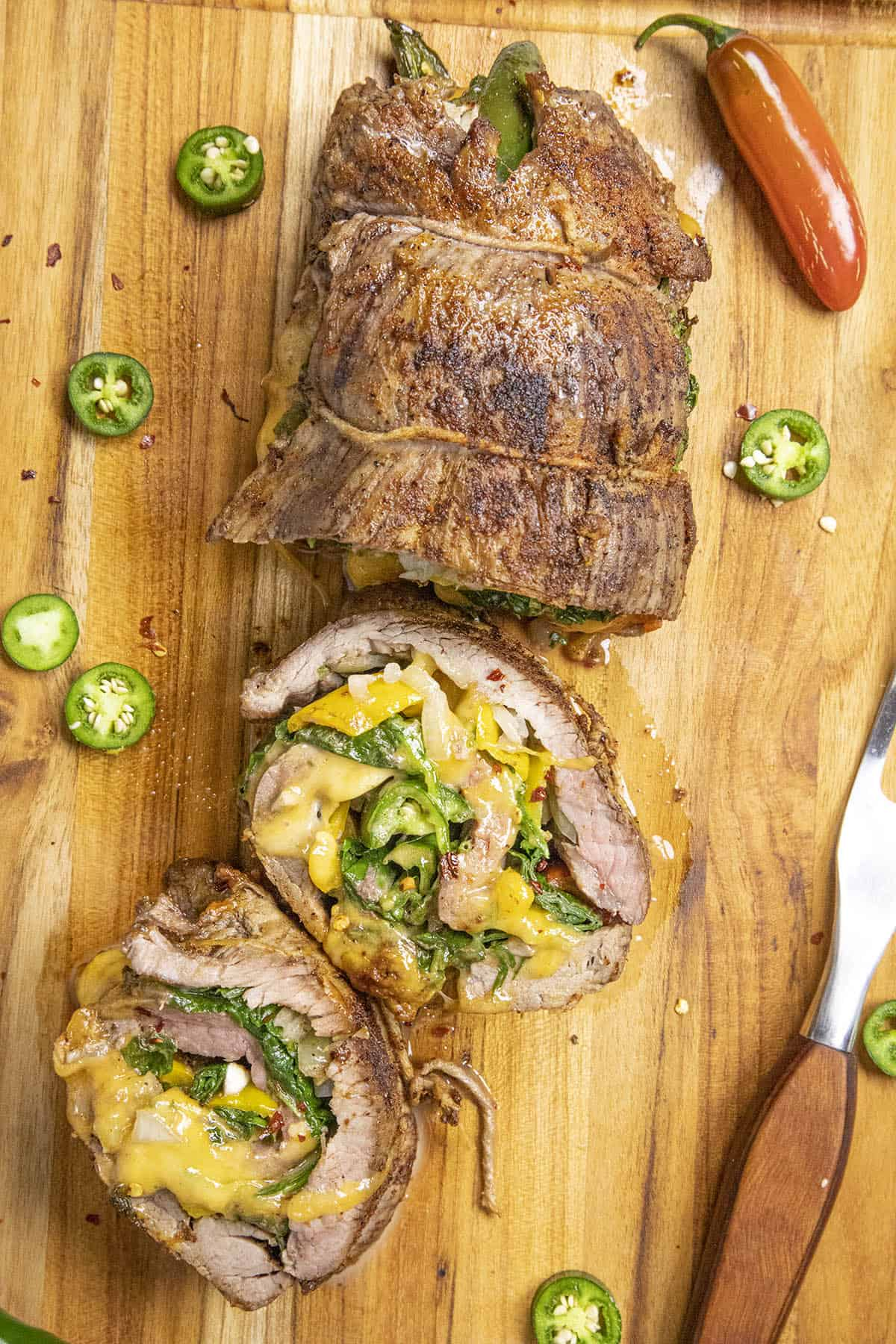 Spinach, Cheese and Chili Stuffed Flank Steak on a cutting board