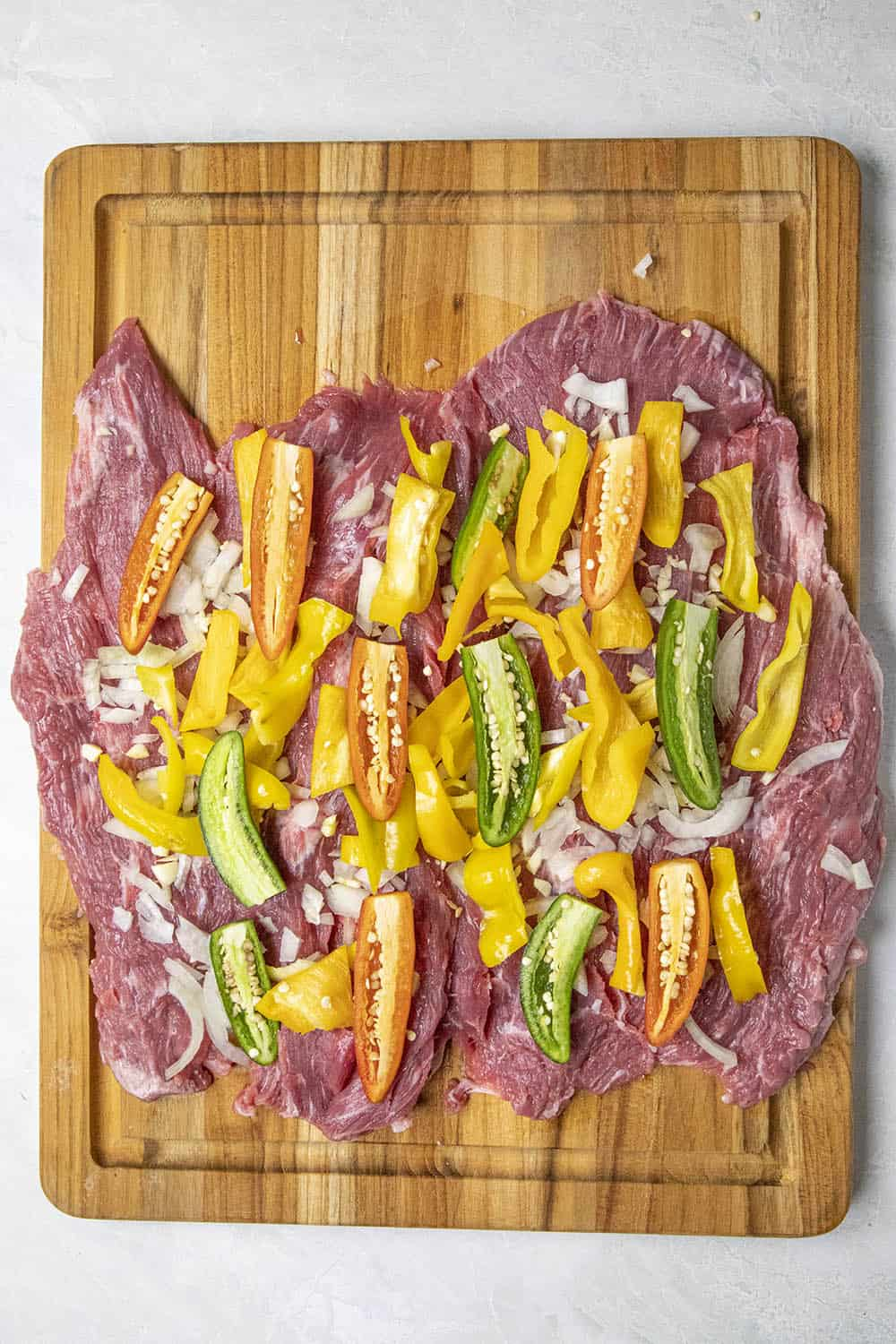 Adding peppers to the flank steak