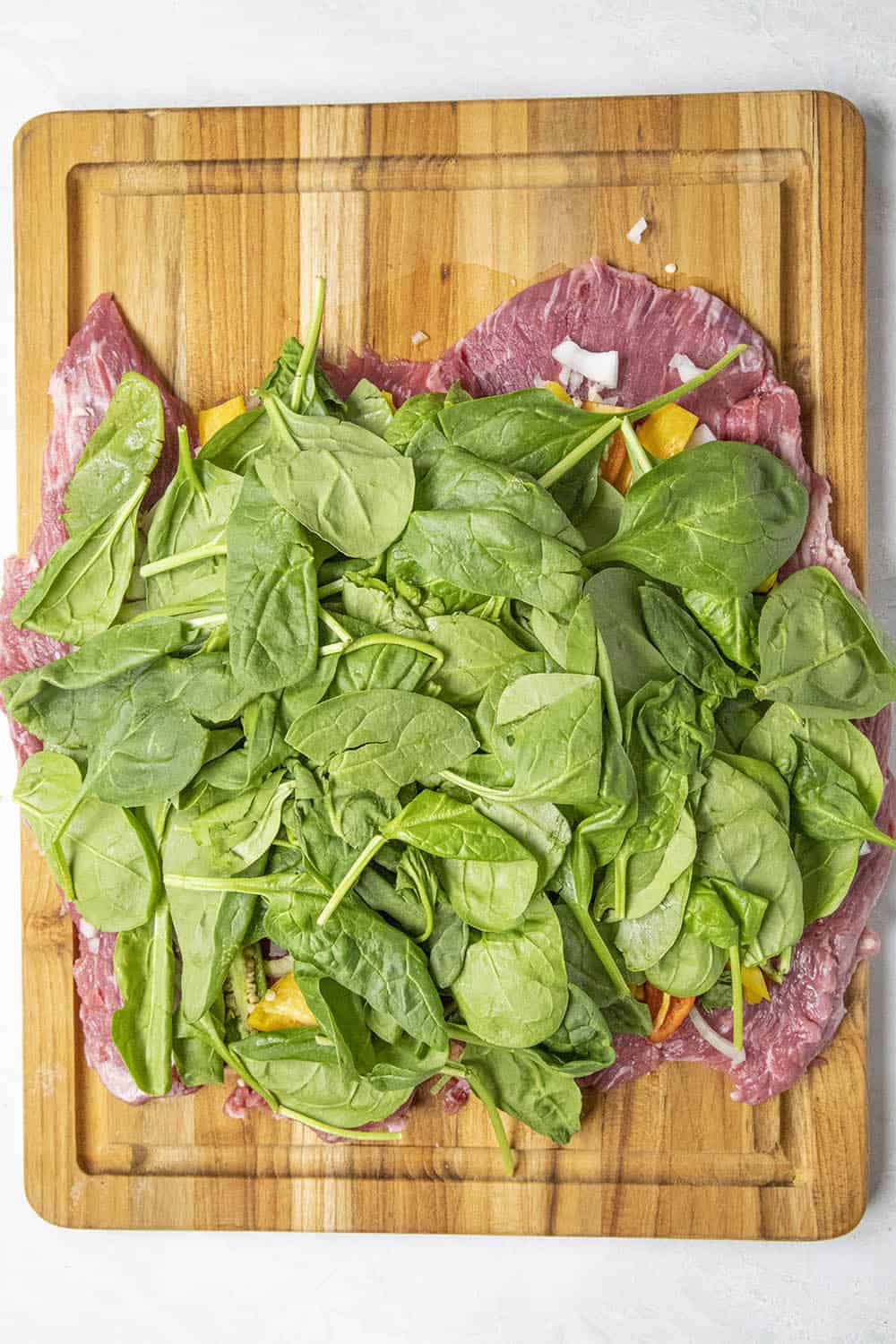 Adding spinach to the flank steak