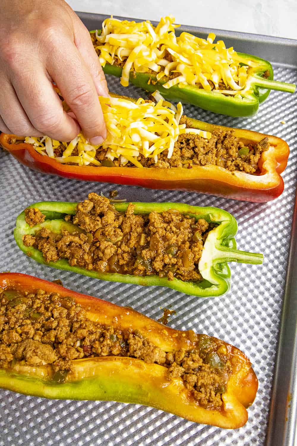 Topping the stuffed peppers with cheese