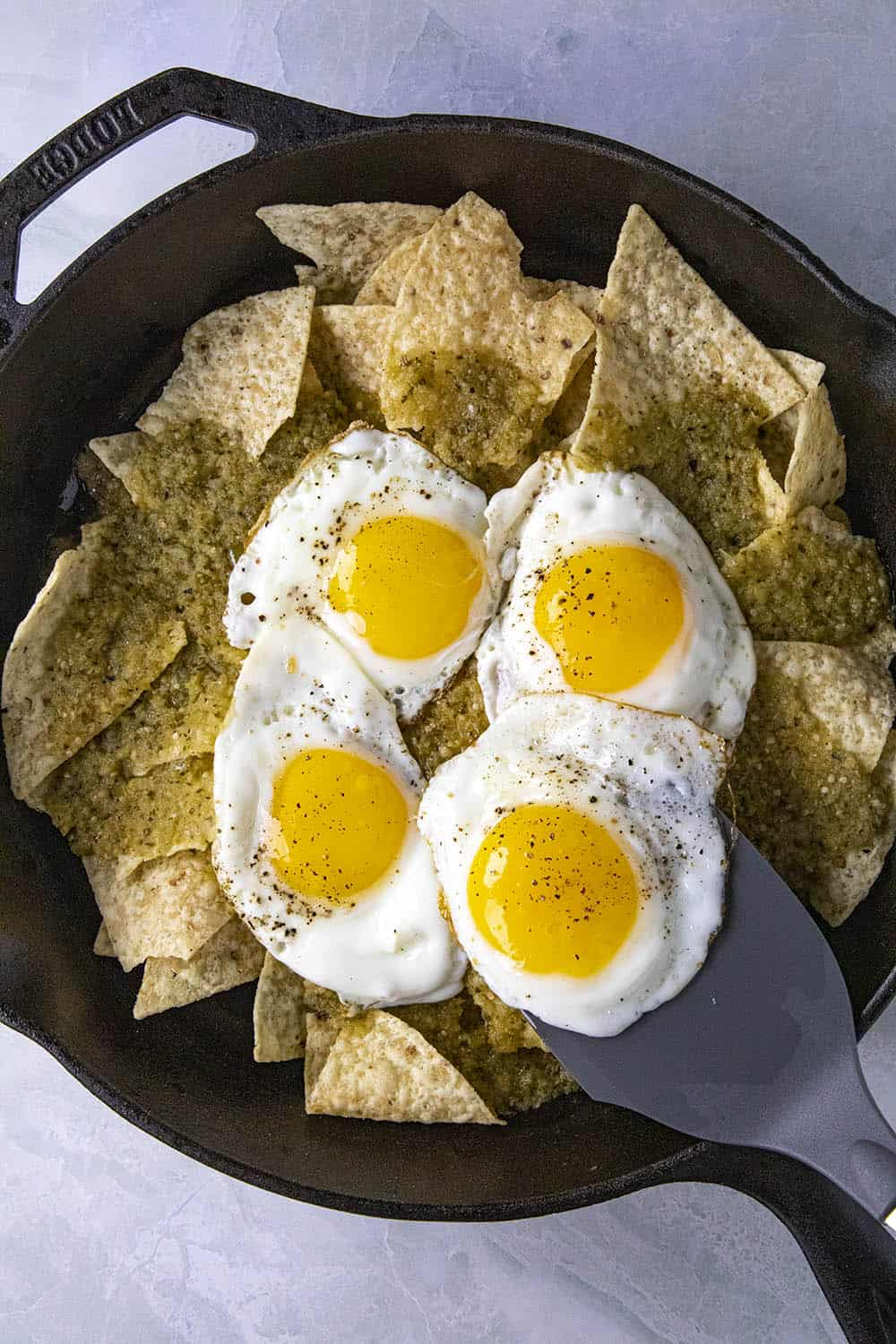 Topping the tortillas with fried eggs