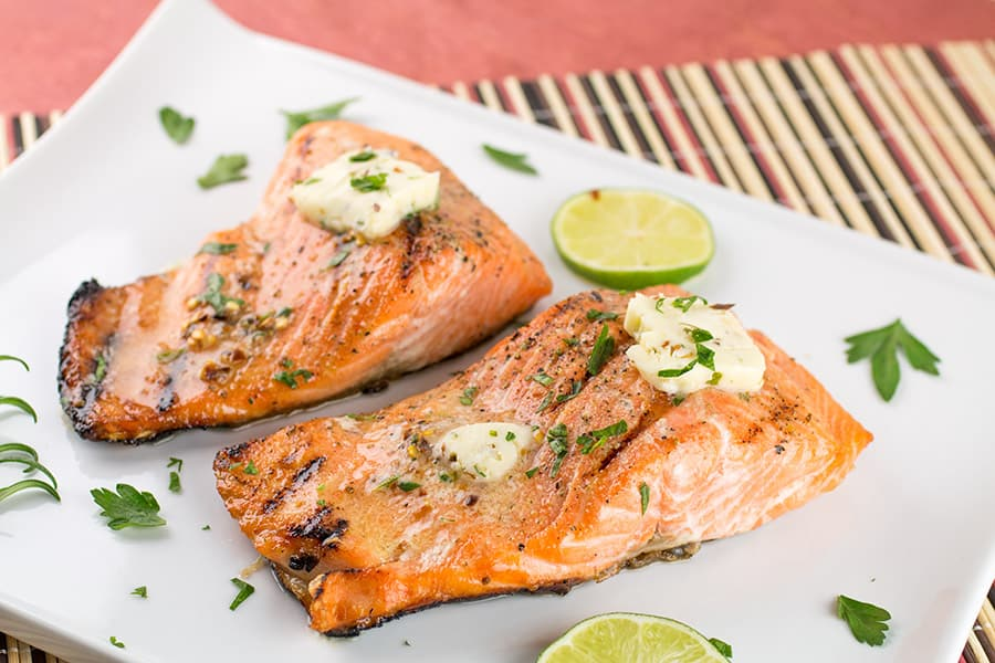 Grilled Steelhead Trout Recipe on a plate with melted butter
