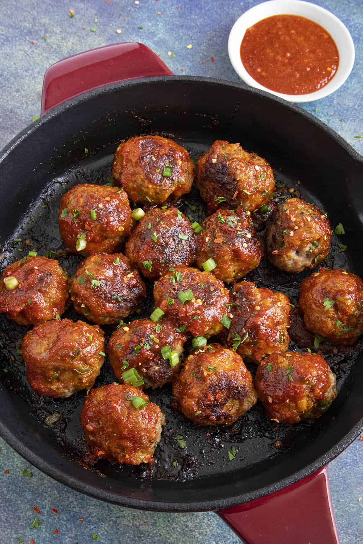 Honey Sriracha Turkey Meatballs in a pan with extra sauce