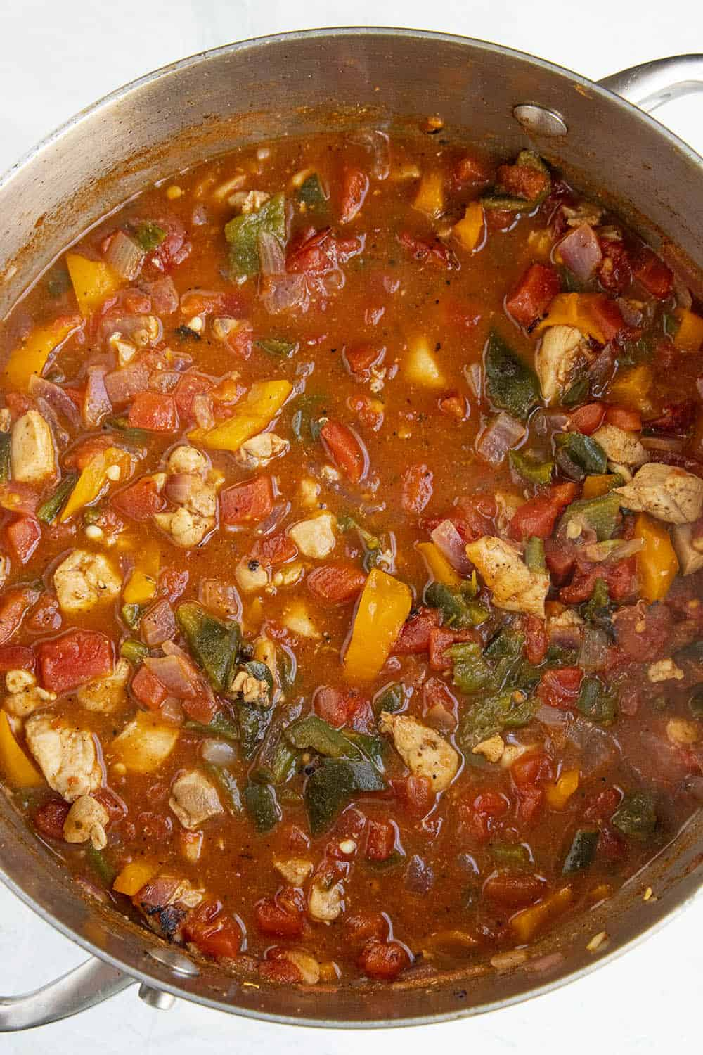 Cooking down the vegetables, chicken and fire roasted tomatoes in a pot