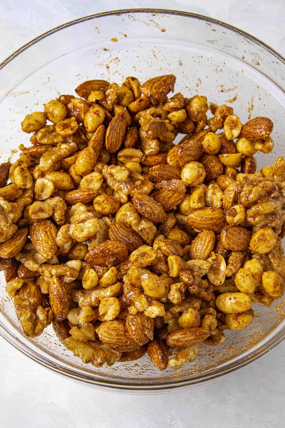 Raw nuts mixed with egg whites and seasonings, ready to bake
