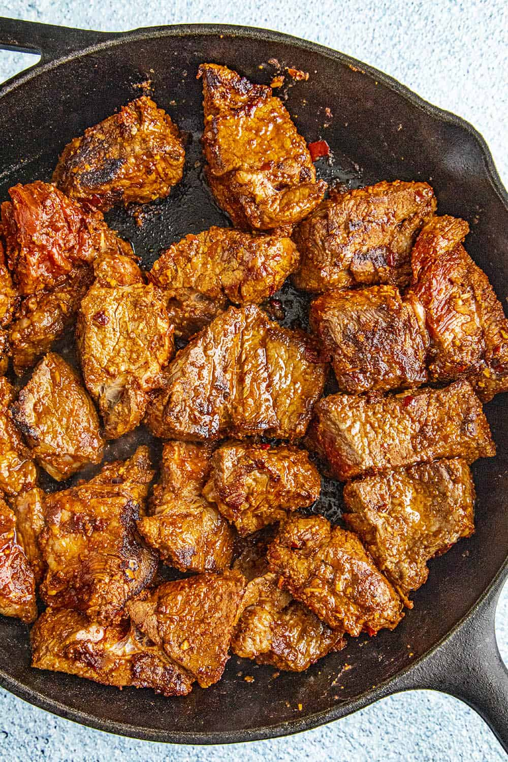 Chunks of seasoned meat seared in a cast iron pan