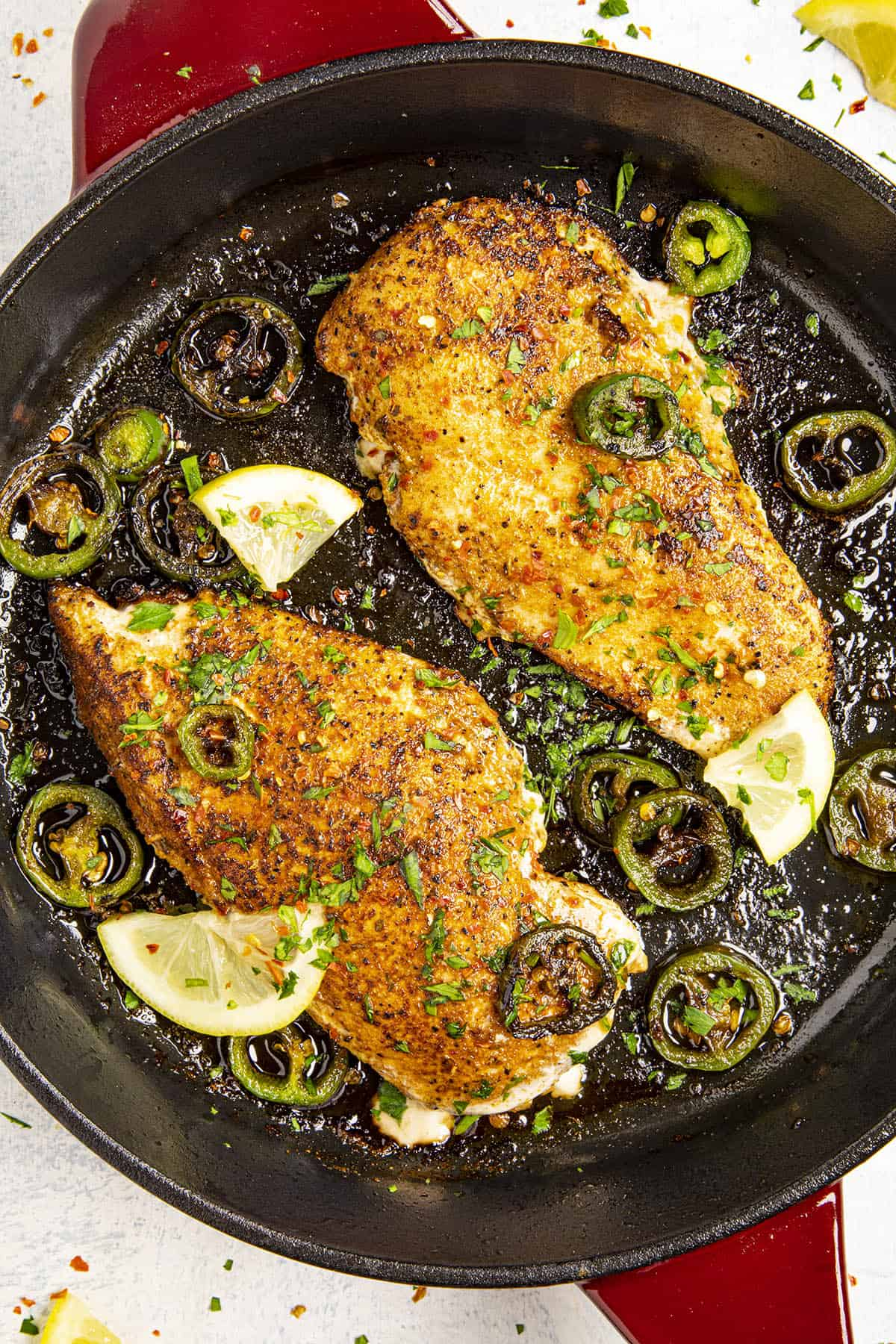 Two Blackened Chicken in a pan with seared jalapenos and lemon slices