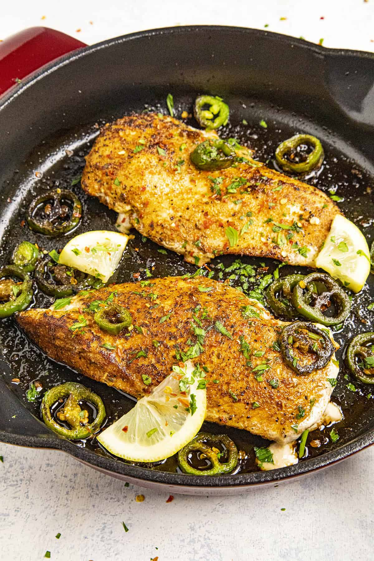 Two Blackened Chicken breasts in a pan