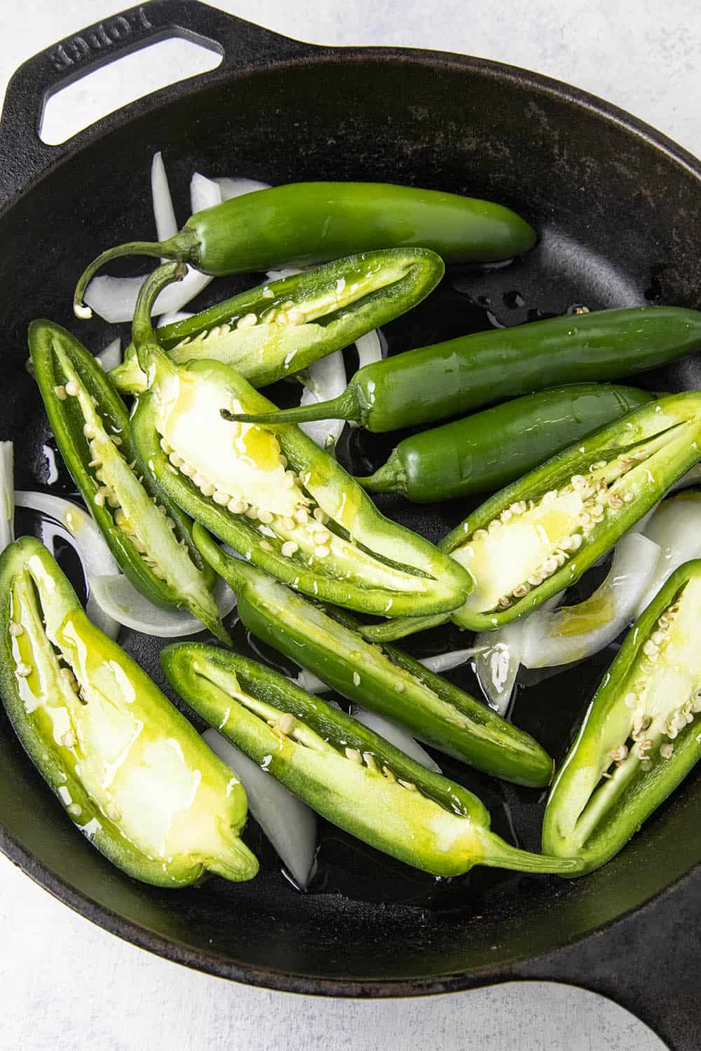 Drizzling olive oil over the jalapeno and serrano peppers in a hot pan