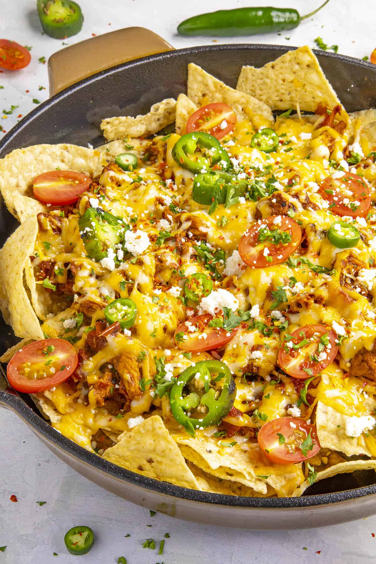 Chipotle Chicken Nachos in a pan with lots of toppings