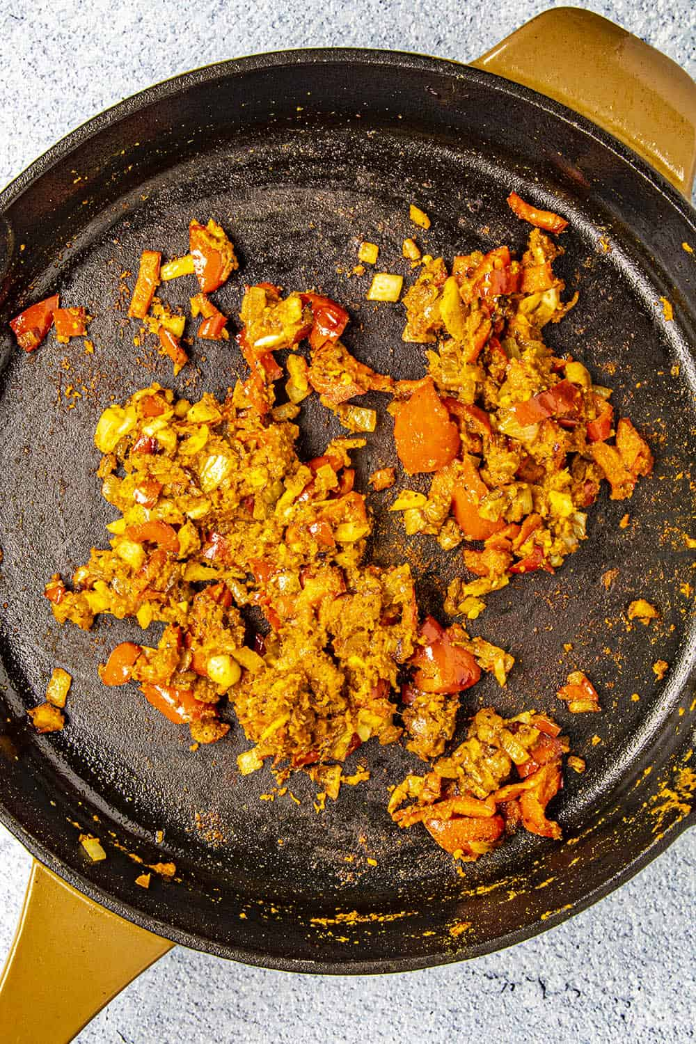 Cooking down the vegetables and red curry paste in a pan