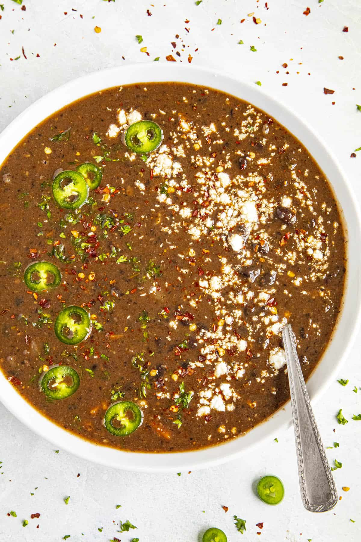 Black Bean Soup garnished with sliced peppers and crumbly white cheese