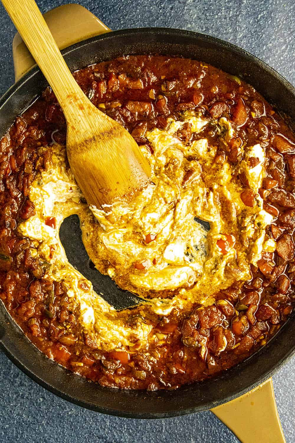 Swirling sour cream into the paprika sauce
