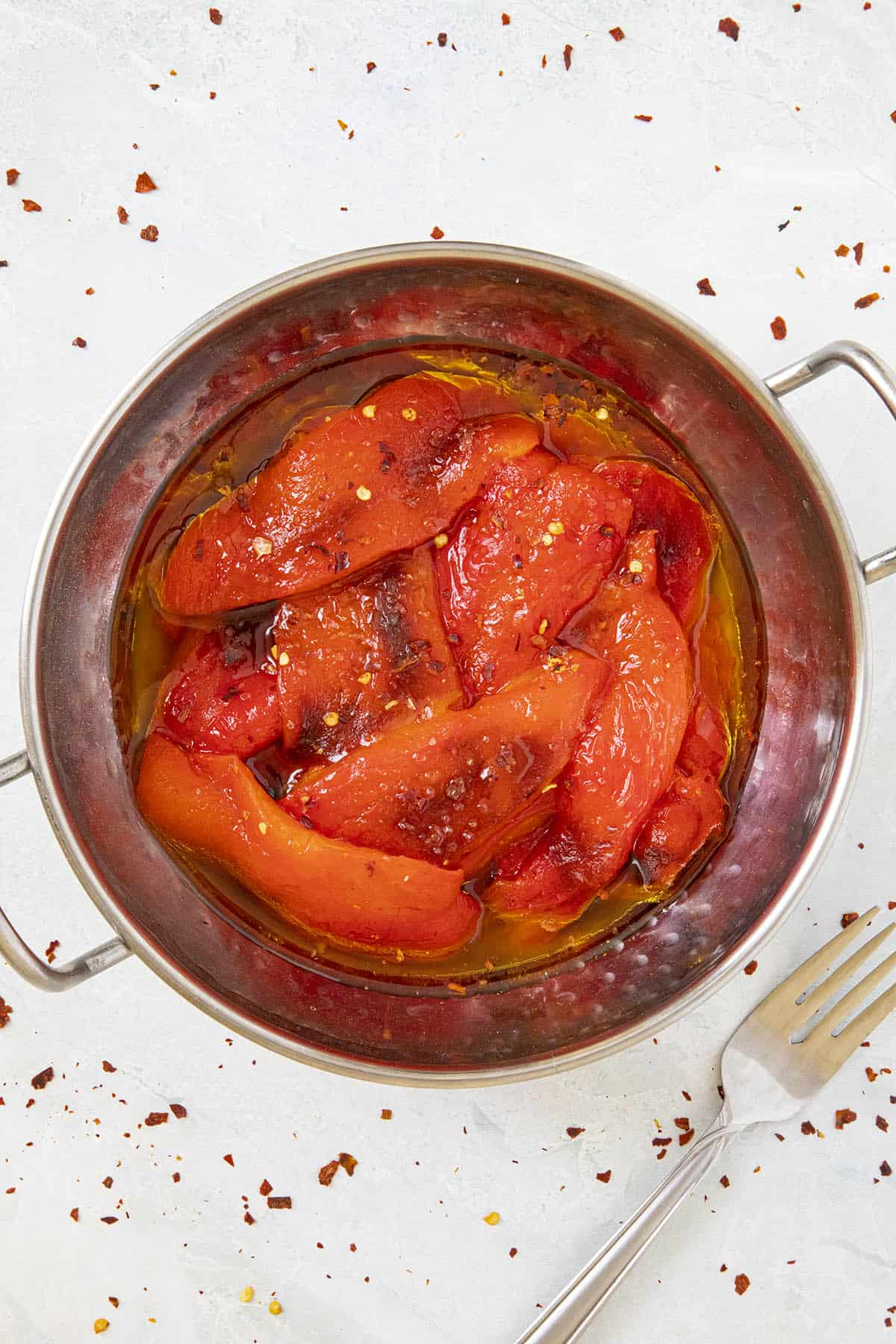 Roasted Red Peppers in a bowl with lots of olive oil, sprinkled with chili flakes