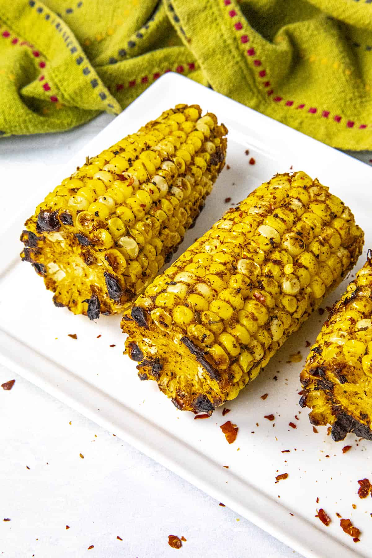 Sliced grilled corn on the cob with lots of seasonings