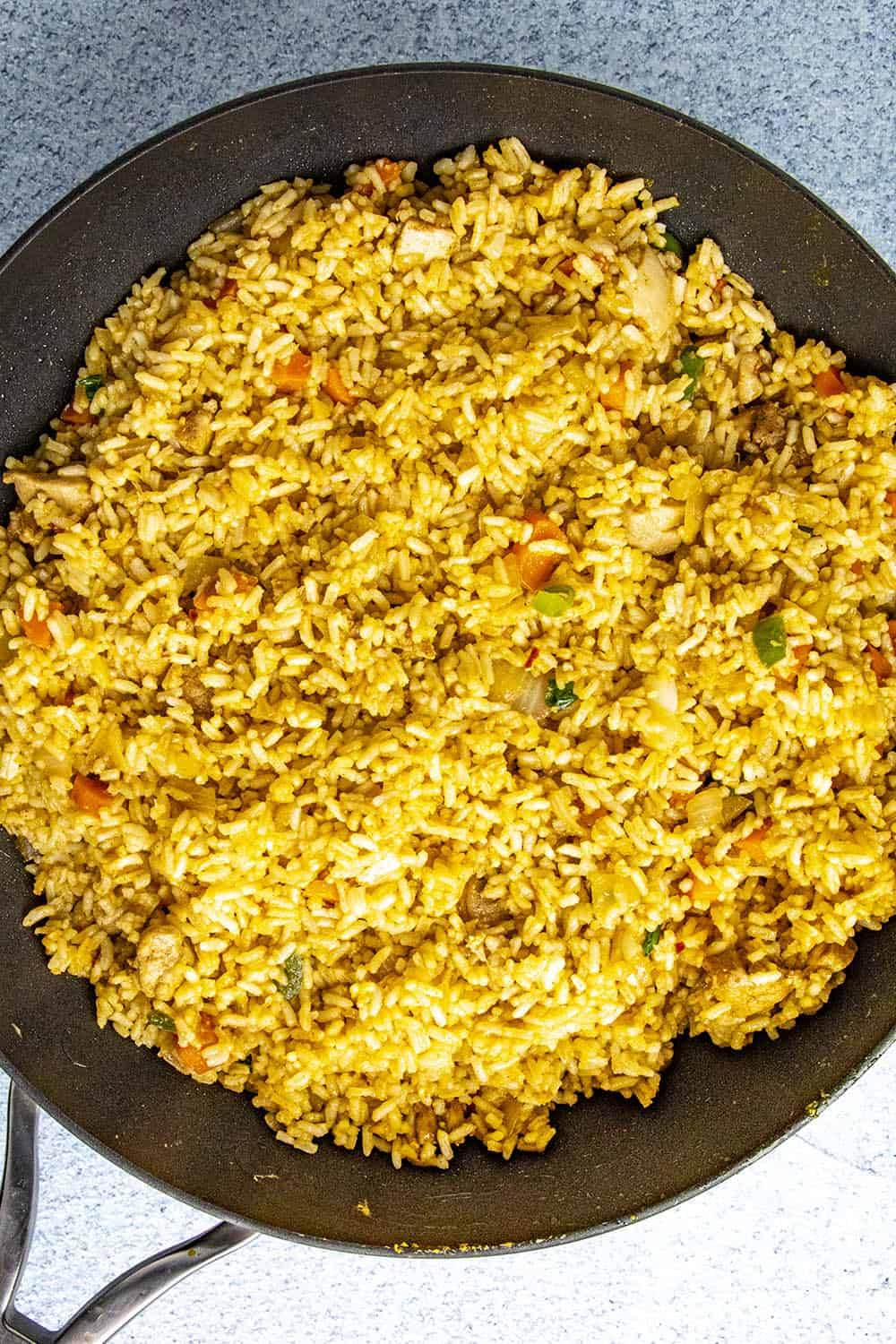 Adding the cooked rice to the hot pan with the chicken and vegetables