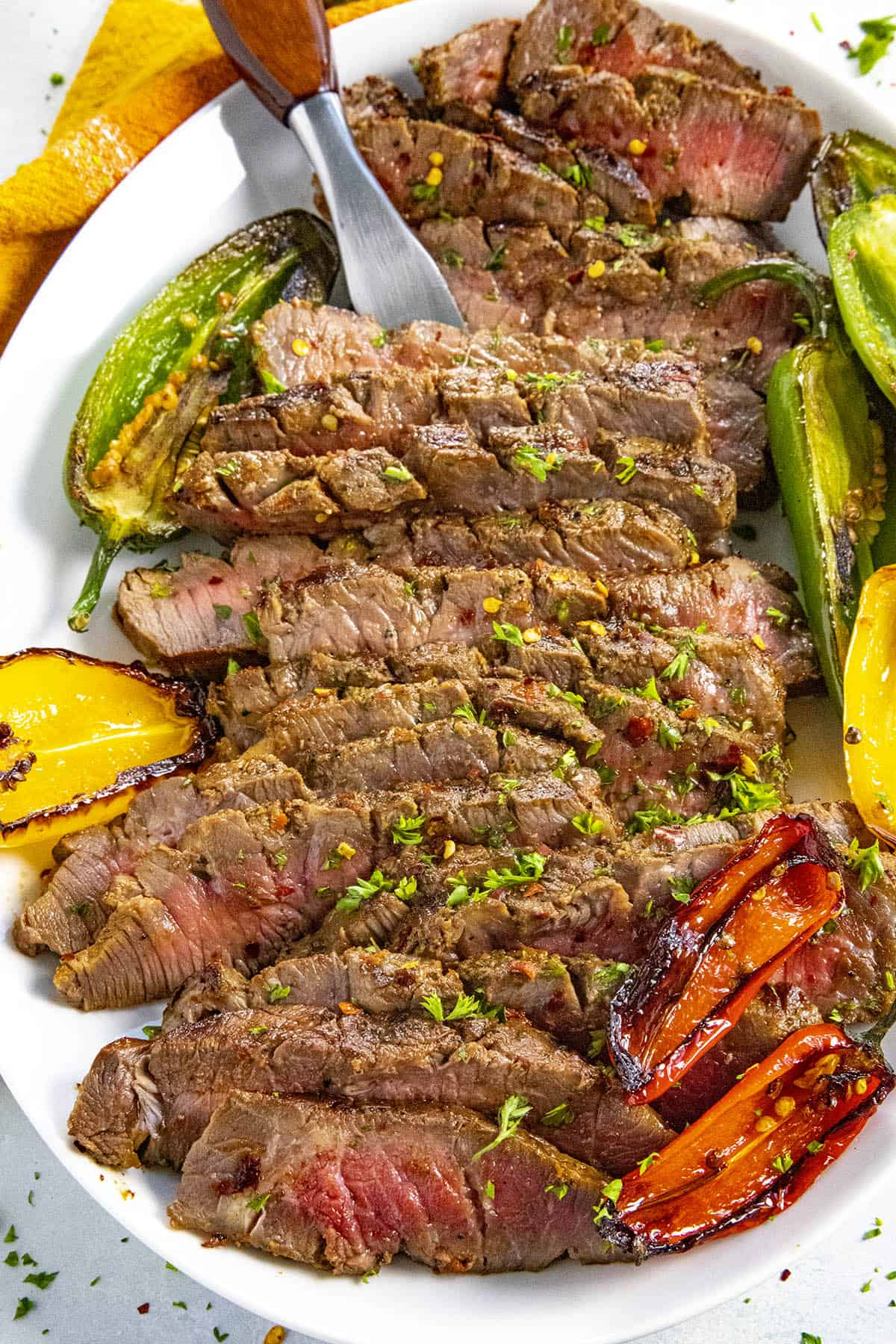 Serving sliced London broil on a platter with grilled peppers